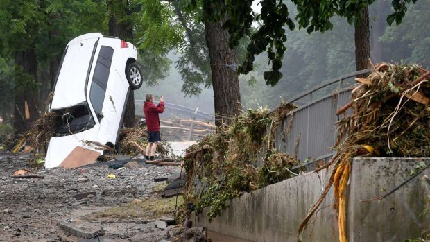 A man standing next to a destroyed car takes pictured of the devastated area after the floods caused major damage in Bad Neuenahr-Ahrweiler. Photograph: AFP via Getty Images