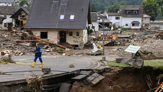 A man walks on a partially slipped road amid destroyed houses after the floods caused major damage in Schuld near Bad Neuenahr-Ahrweiler. Photograph: AFP via Getty Images