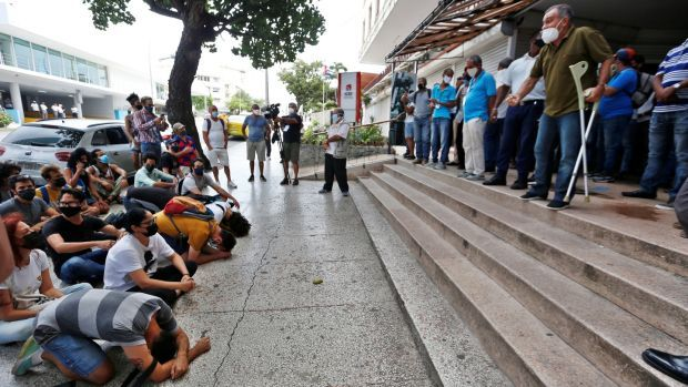 Demonstrators (L) protest in front of workers of the Institute of Radio and Television in Havana, Cuba. Photograph: Ernesto Mastrascusa/EPA