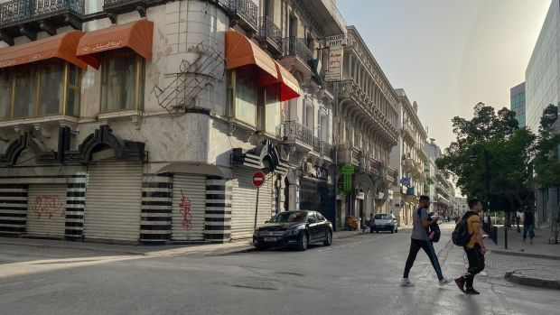 Pedestrians walk the streets of Tunis. Shops were shuttered in the city ahead of a newly extended curfew. Photograph: Sima Diab/The New York Times