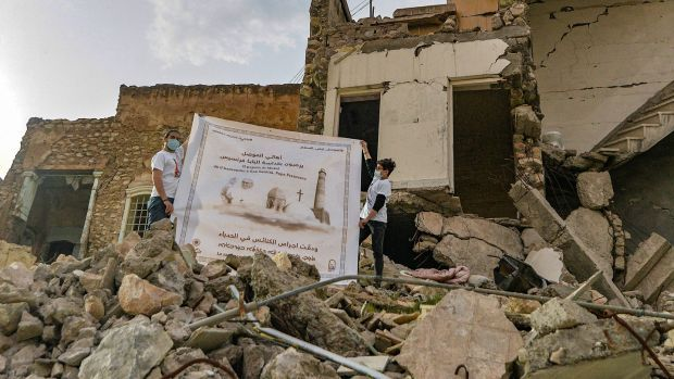 Youths unfurl a poster welcoming Pope Francis above the rubble of a destroyed house next to the ruins of the Syriac-Catholic Church of the Immaculate Conception (al-Tahira) in the old city of Iraq's northern city of Mosul in March. Photograph: Zaid al-Obeidi/AFP via Getty Images