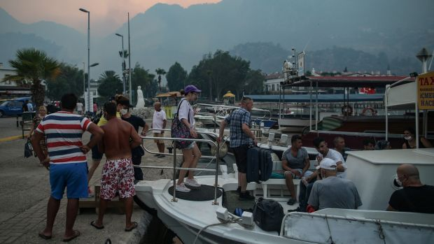 Tourists leave Turunc, in the Marmaris district of Mugla province, by boat on Sunday due to wildfires. Photograph: Erdem Sahin/EPA