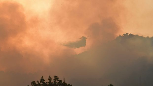 An aircraft drops water during a wildfire in ancient Olympia, western Greece. 'Our forces fought an all-night battle . . . to keep the archaeological site and the town intact.' Photograph: Giannis Spyrounis/ilialive.gr via AP