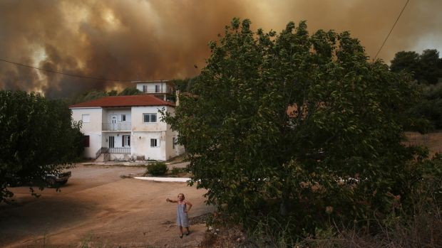 A woman speaks to media during a wildfire in Viliza village in the area of Ancient Olympia, Peloponnese, Greece. Photograph: Orestis Panagiotou/EPA