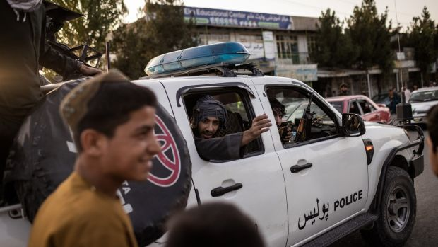 Taliban fighters drive into Kabul. Photograph: Jim Huylebroek/The New York Times