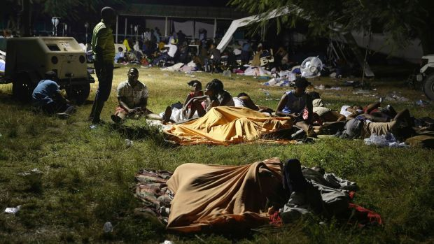 People displaced from their earthquake-destroyed homes spend the night outdoors in a grassy area in Les Cayes. Photograph: Joseph Odelyn/AP