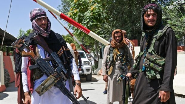 Taliban fighters stand guard along a roadside near the Zanbaq Square in Kabul on Monday. Photograph: Wakil Kohsar/AFP via Getty Images