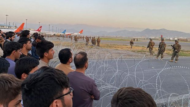 Afghans crowd at the airport as US soldiers stand guard in Kabul on Monday. Photograph: Shakib Rahmani/AFP via Getty Images