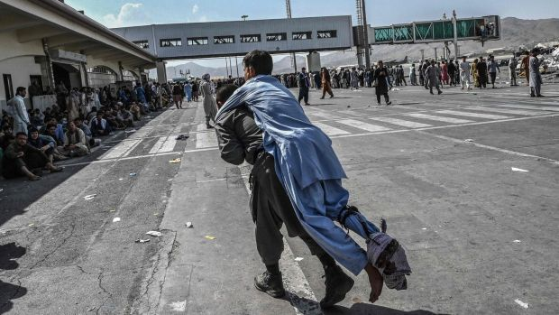 A volunteer carries an injured man as other people can be seen waiting at the Kabul airport in Kabul. Photograph: Wakil Kohsar / AFP / Getty Images