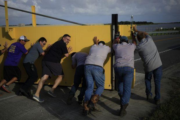 Crews work to secure a levee flood gate across Louisiana Route 1 ahead of Hurricane Ida. Photograph: Luke Sharrett/Bloomberg