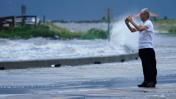 A spectator photographs the flood waters at the Port Gulfport Marina as they watch the arrival of Hurricane Ida Sunday, in Gulfport, Mississippi. Photograph: Steve Helber/AP