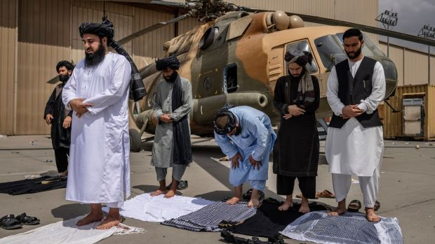 Members of the Taliban during prayer in front of a disabled helicopter at the airport in Kabul. Photograph: Victor J Blue/The New York Times