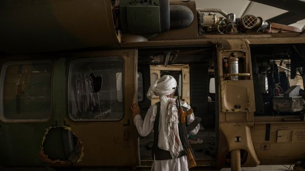 A Taliban member inspects a damaged helicopter at the airport in Kabul on Tuesday. Photograph: Victor J Blue/The New York Times