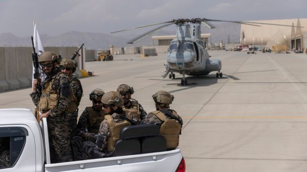 Taliban fighters secured helicopters that had been disabled and left behind by American forces. Photograph: Victor J Blue/The New York Times