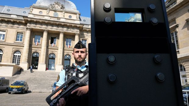 A police officer behind a shield outside the Paris courthouse last week. Photograph: Francois Mori/AP Photo