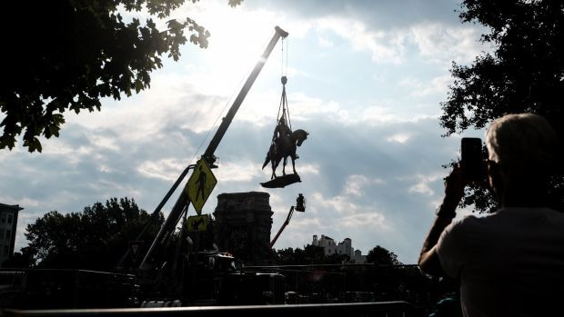 The statue of Robert E Lee being removed from its pedestal in Richmond, Virginia. Photograph: Michael A McCoy/New York Times