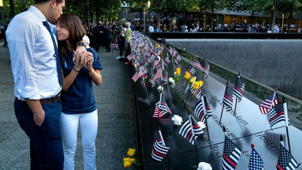 Katie Mascali is comforted by her fiance Andre Jabban as they stand near the name of her father, Joseph Mascali, during 9/11 commemoration ceremonies in New York. Photograph: Craig Ruttle/Pool/AFP/Getty