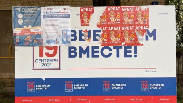A Moscow sign saying 'Let's choose together!' ahead of Sunday's Russian parliamentary elections, which has been covered over with posters for a Communist Party candidate and offers of prizes to people who register to vote online.