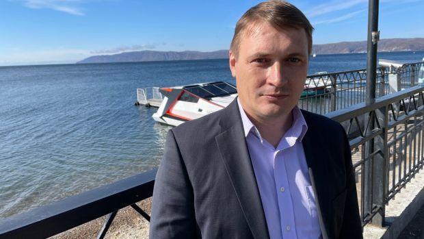 The newly elected mayor of Listvyanka, Maxim Maximov, stands on the shore of Lake Baikal in Siberia