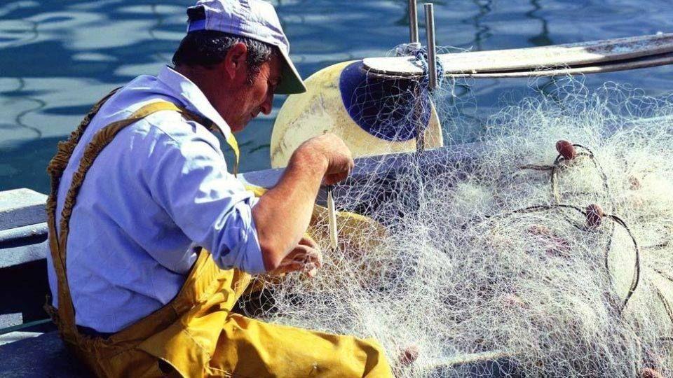 Pêcheur en train de démêler ses filets de pêche