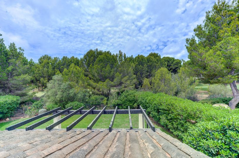 This beautiful villa directly on the golf course is located on a 635m2 plot in a popular complex in Santa Ponsa and has its own pool