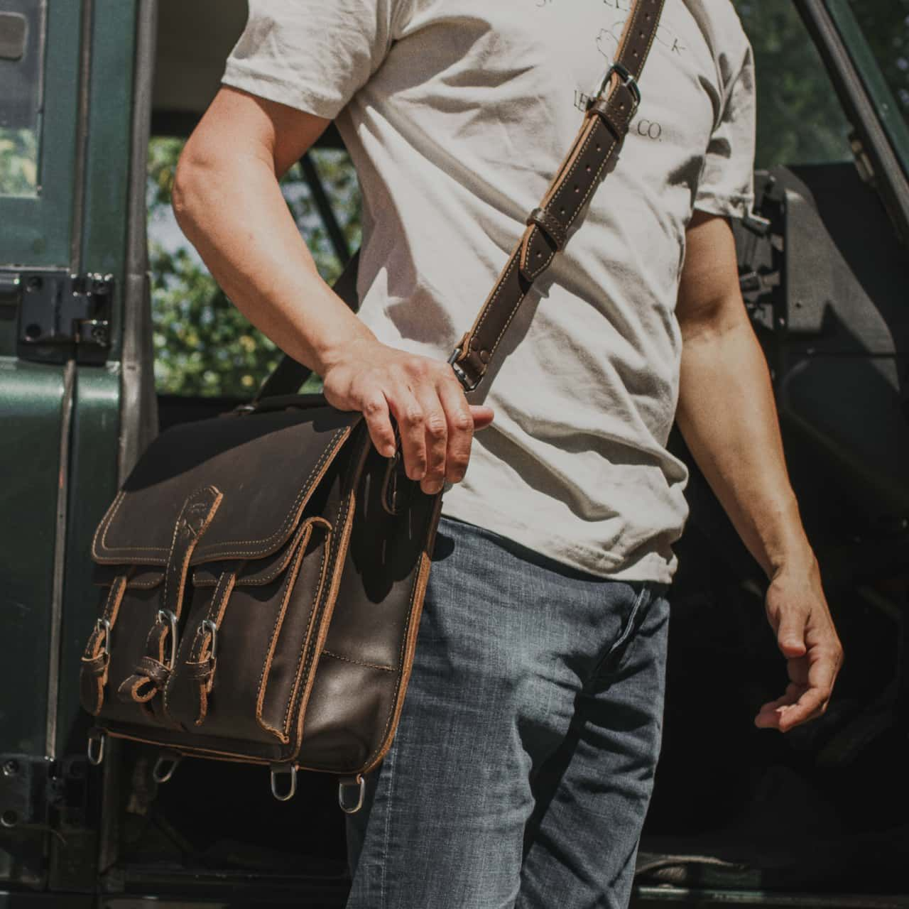 A man in a light shirt and dark jeans with a hanging thin front pocket leather briefcase medium in dark coffee brown leather on his shoulder