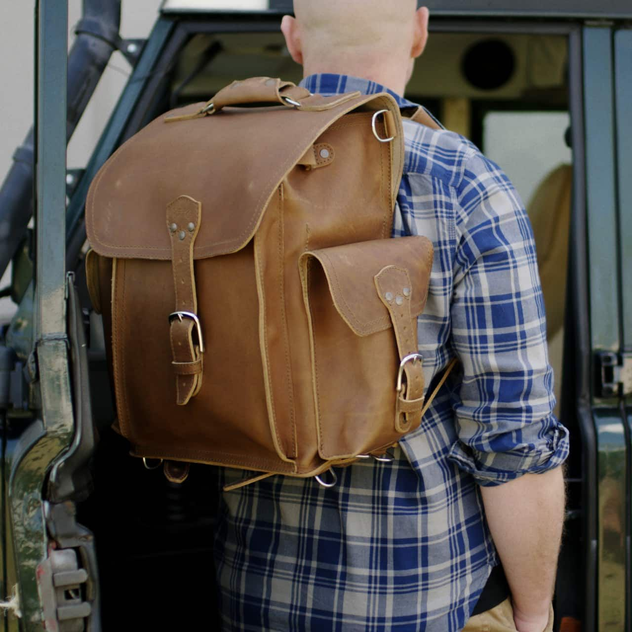 A man with a squared leather backpack in tobacco leather on his back wearing a shirt standing in front of a car
