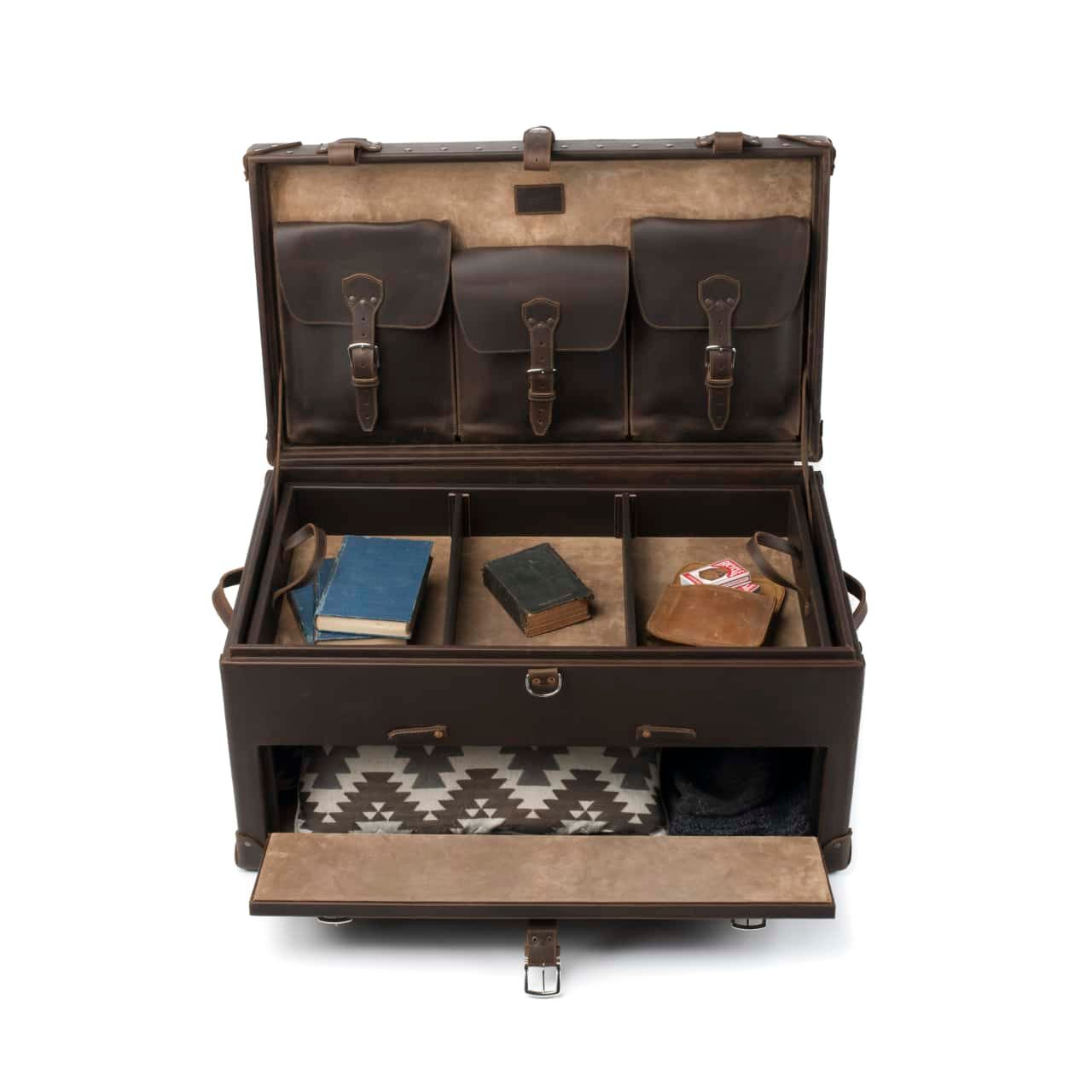 Leather Trunk in color Dark Coffee Brown shown from the Front Top with the Upper and Bottom Lids Open with Books Cards Pillows and Blankets