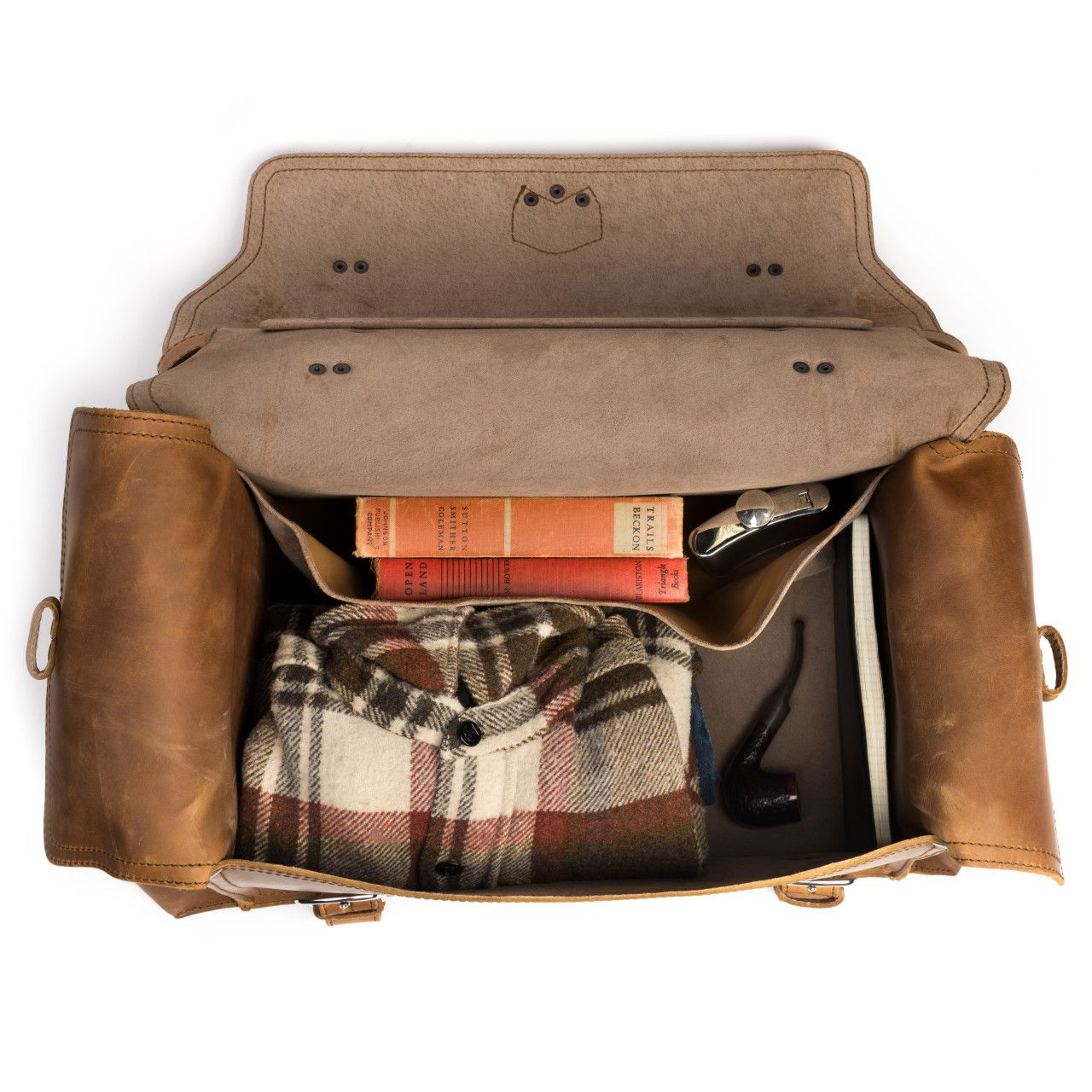 side pocket leather duffel bag large in tobacco leather with books, a shirt and a pipe in the interior