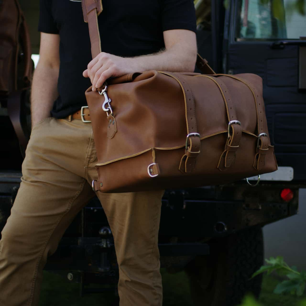 A man wearing a black t-shirt and holding a hand in his pocket and carrying a waterbag premium leather duffel bag medium in tobacco leather on his shoulder