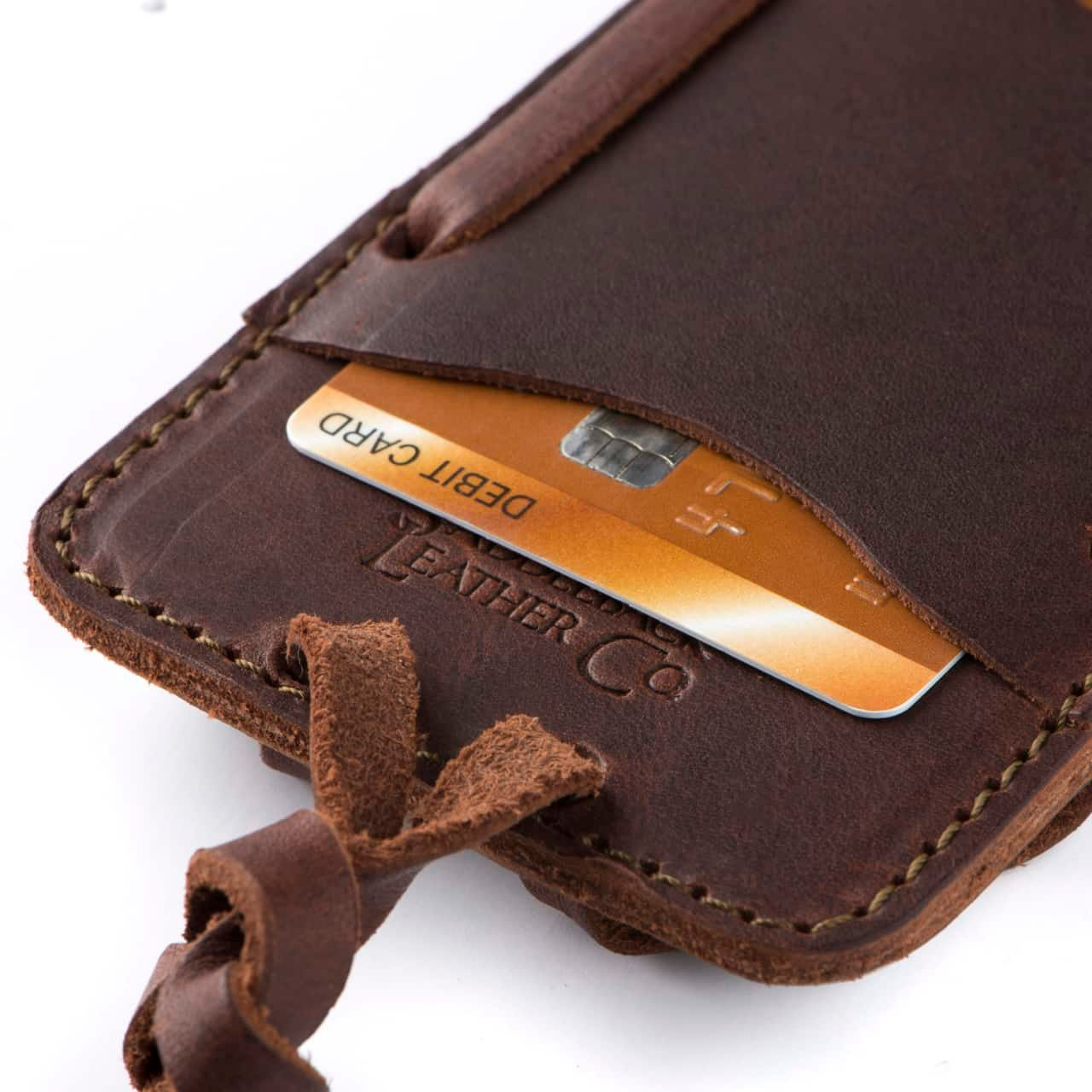 Leather iPhone 8 Case in Color Chestnut Zoomed in on the Saddleback Logo and Card Slot with a Card