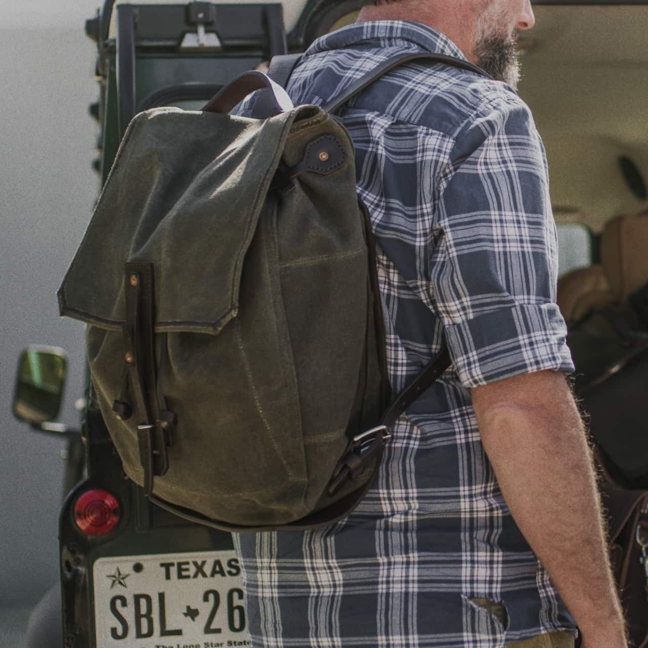 A bearded man in a shirt standing sideways with a waxed canvas backpack small medium in moss green canvas hanging on his shoulder