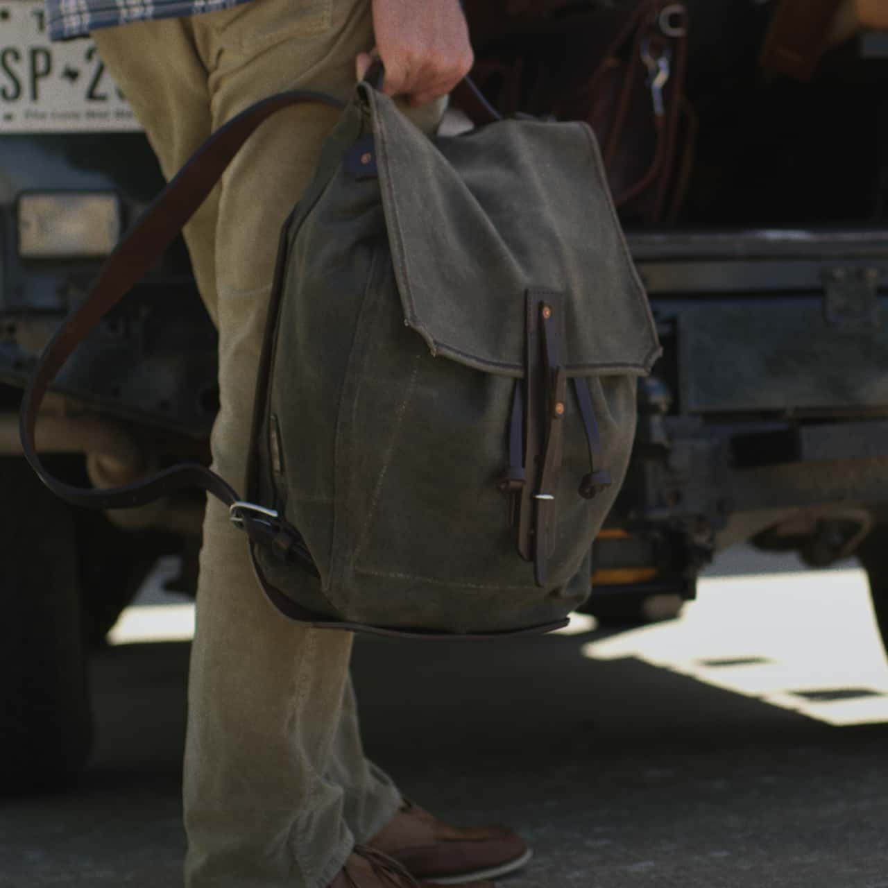 A man in bright trousers standing in front of a car and holding a waxed canvas backpack small medium in moss green canvas in his hand