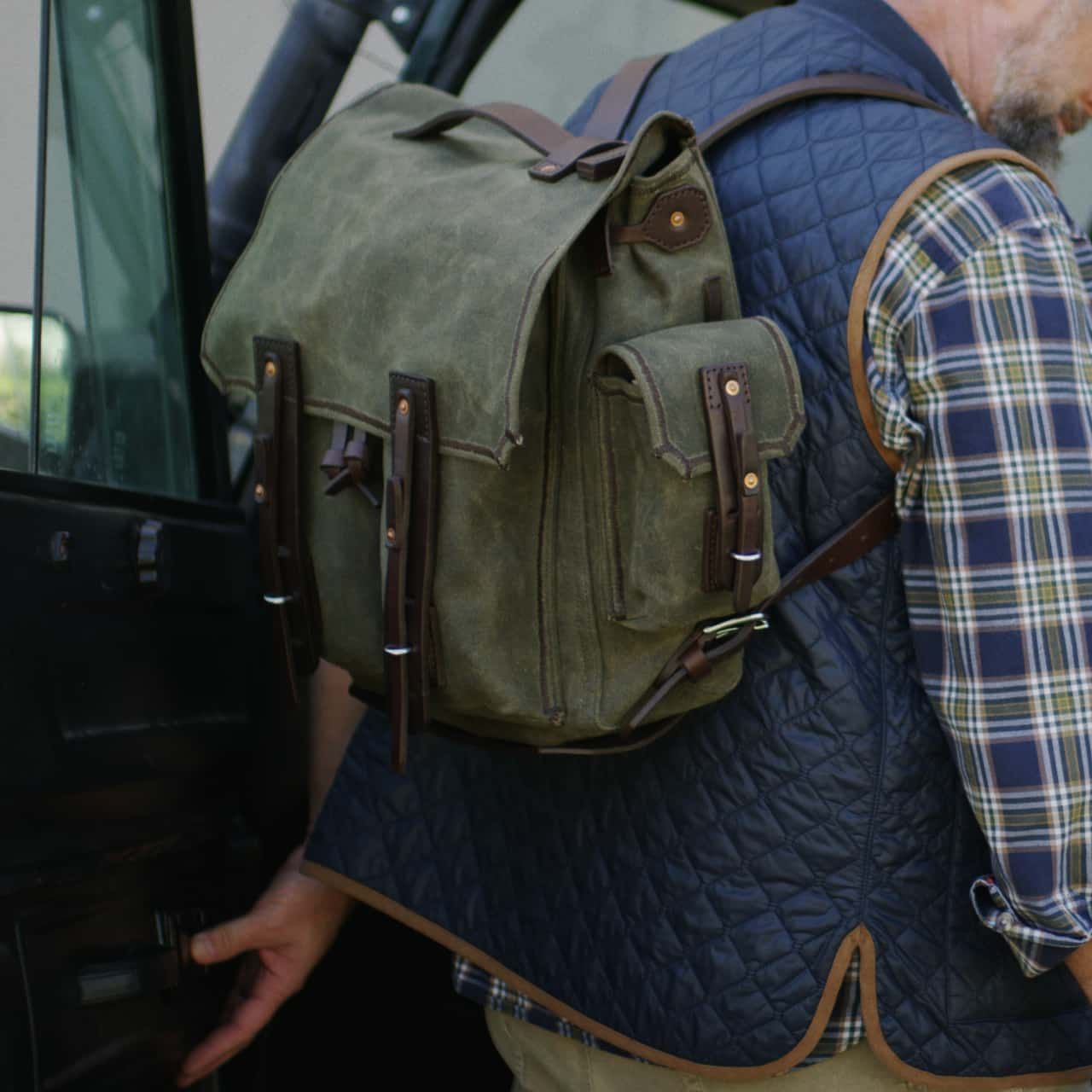 A man wearing a blue vest, holding a left hand car door and a canvas backpack medium in moss green canvas on his back
