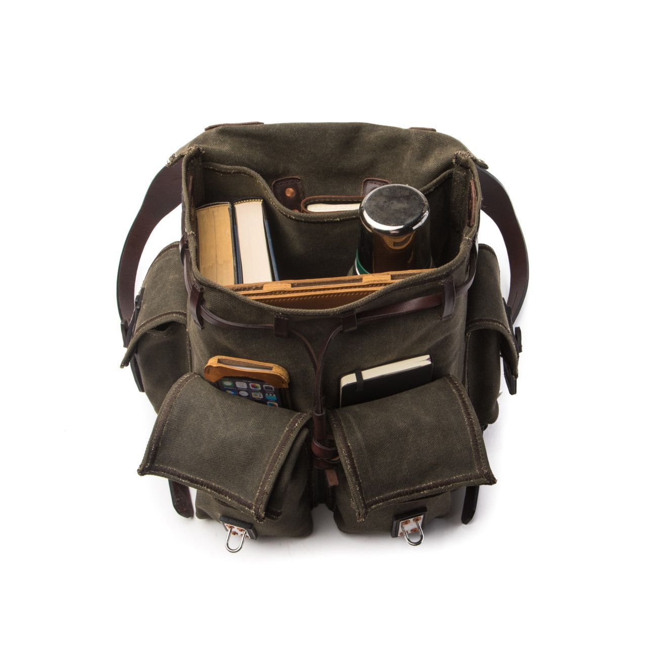 inside the canvas backpack medium in moss green canvas are thermos, books, notepad, iphone