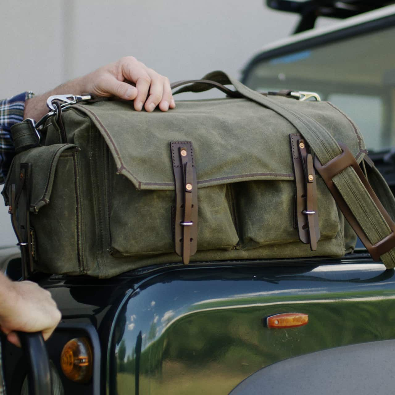 The canvas duffel in moss green canvas is located on the front flap of the green car