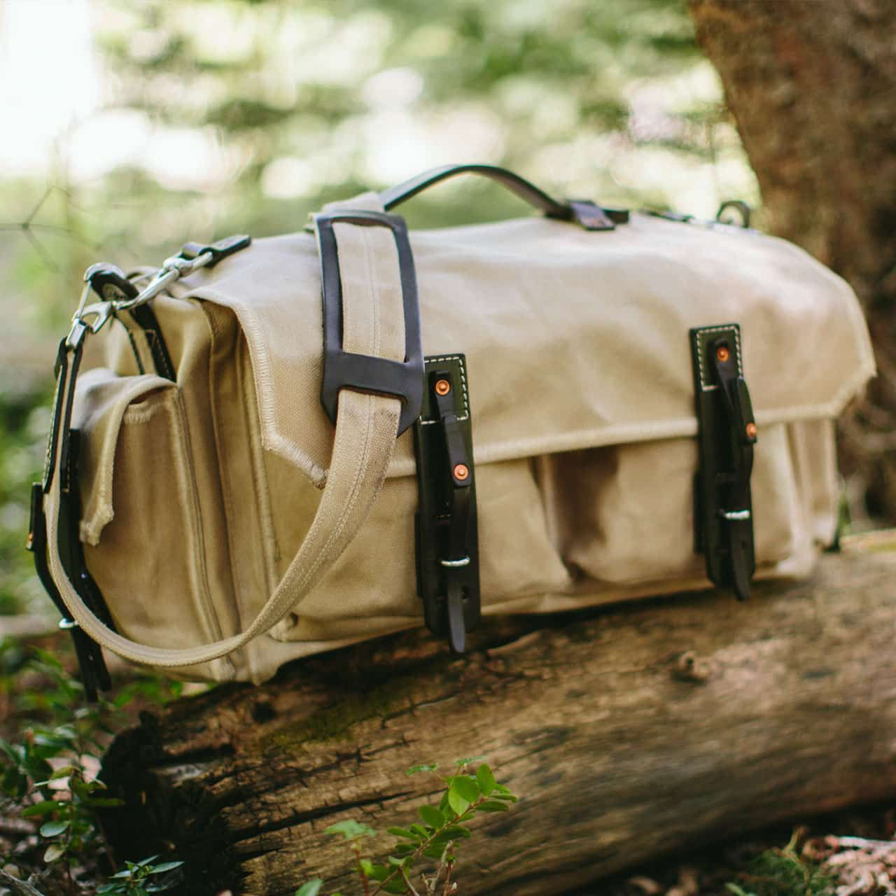 5 Pocket Duffel in Color Sand sitting on a Log
