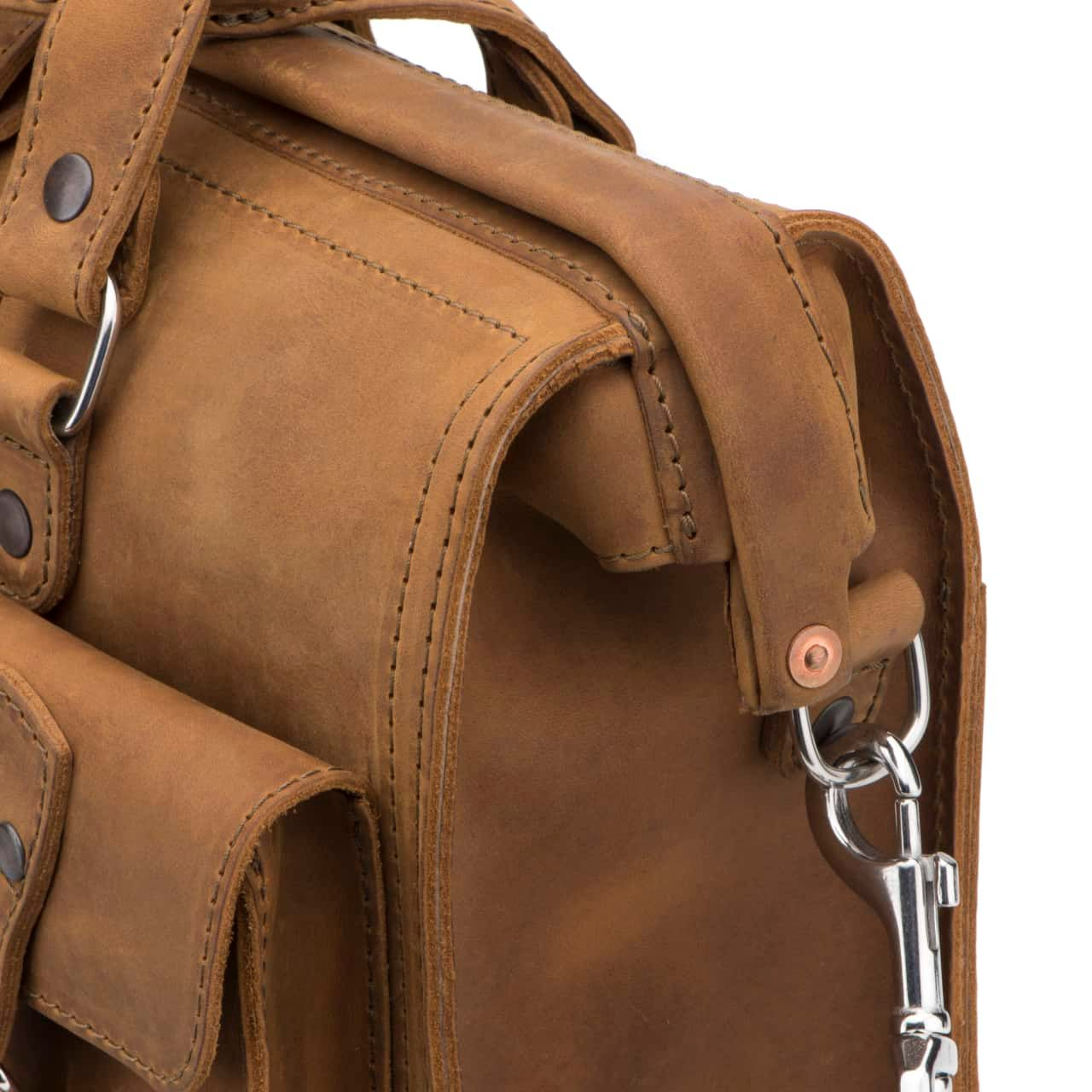 Leather Flight Bag in color Tobacco zoomed in on the Copper Riveted Hinge Closure and D Ring With Attached Strap Clasp