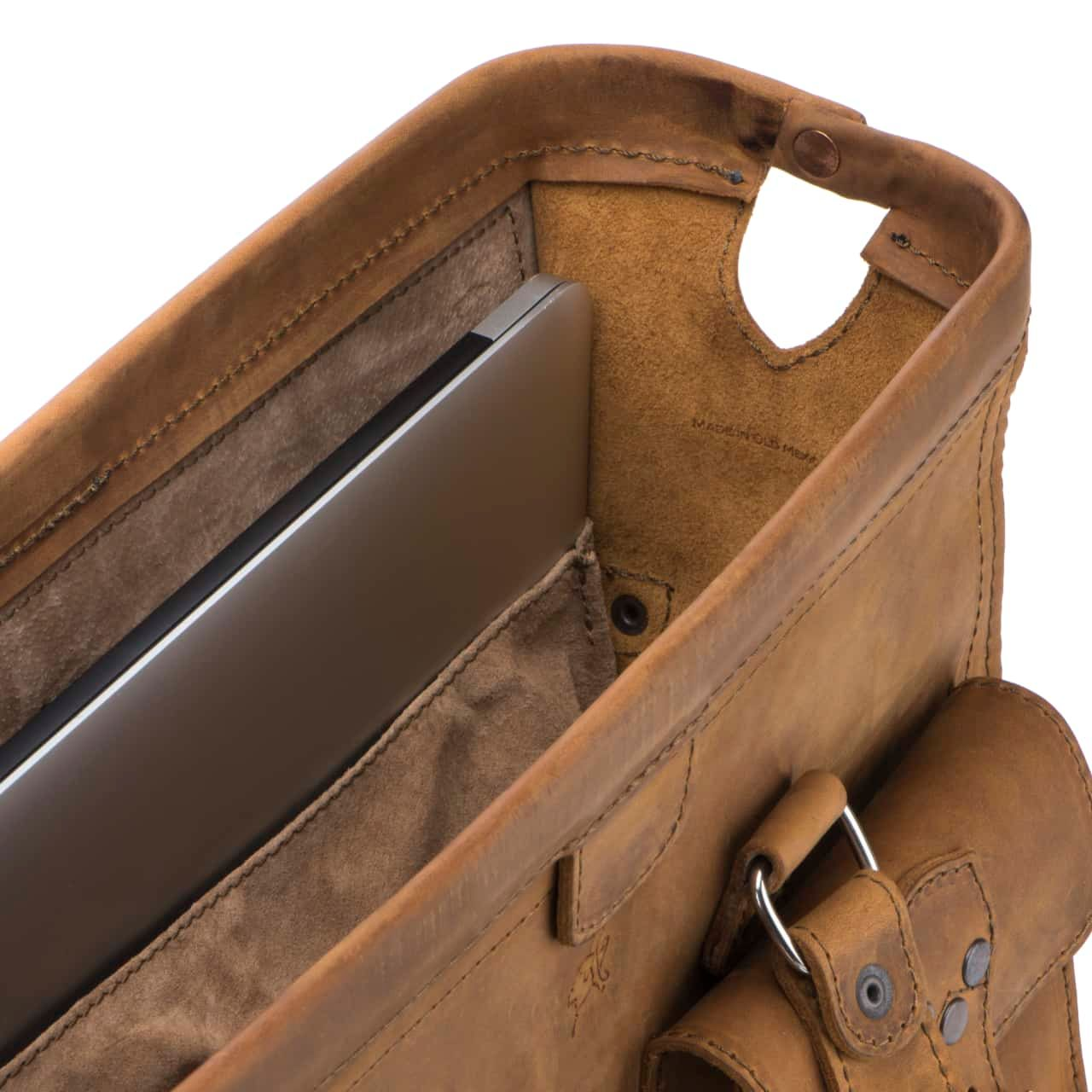 Leather Flight Bag in color Tobacco zoomed in on the Open Hinge Closure with a view of the Interior that has a Laptop