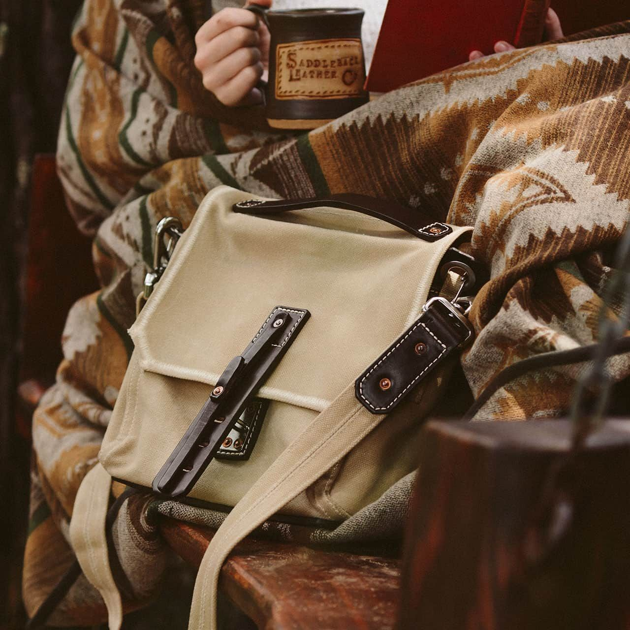 Indiana Gear Bag in Sand sitting next to a book reading coffee wielding woman