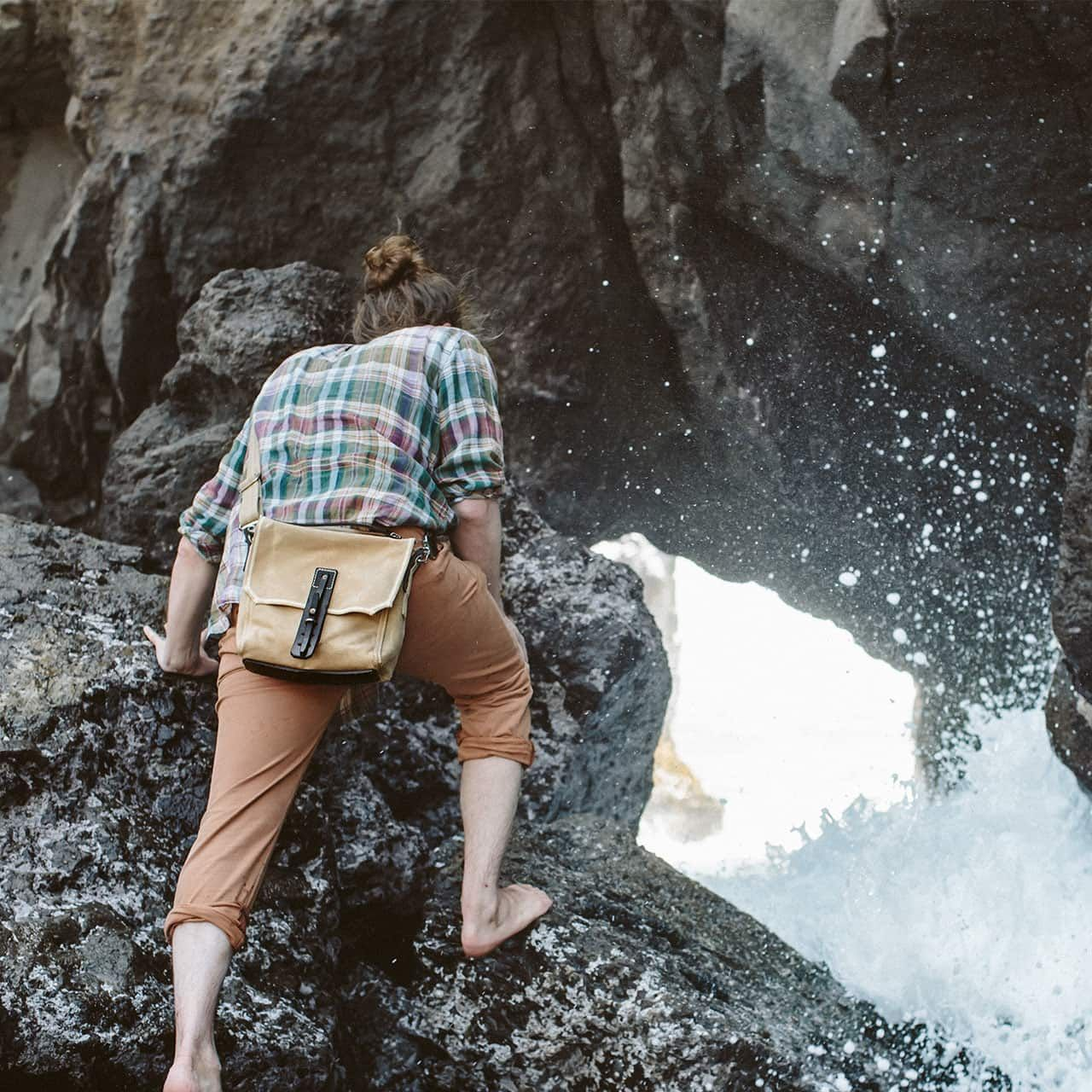 Indiana Gear Bag in Sand Worn CrossBody to the Rear on a Man Climbing Watery Rocks