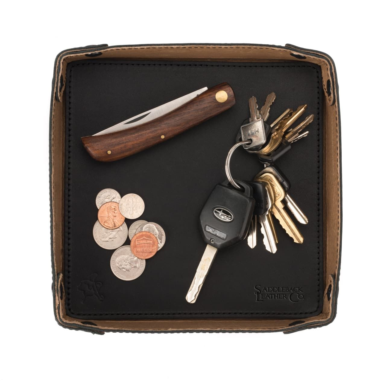 Keys, money and a pocket knife on the leather valet tray in black leather