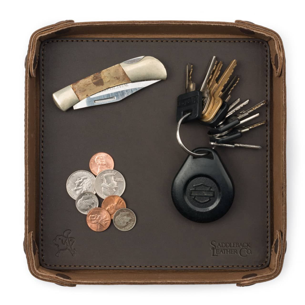 Keys, money and something located on the leather valet tray in dark coffee brown leather