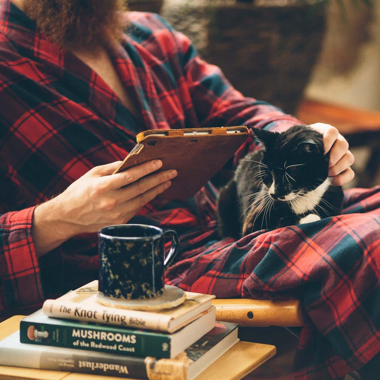 Simple iPad Case in color Tobacco being held by a man in a plaid robe with a cat and coffee