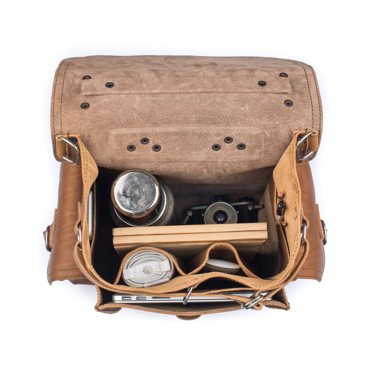An old camera and a macbook with a set to handle the inside of the squared leather backpack in tobacco leather