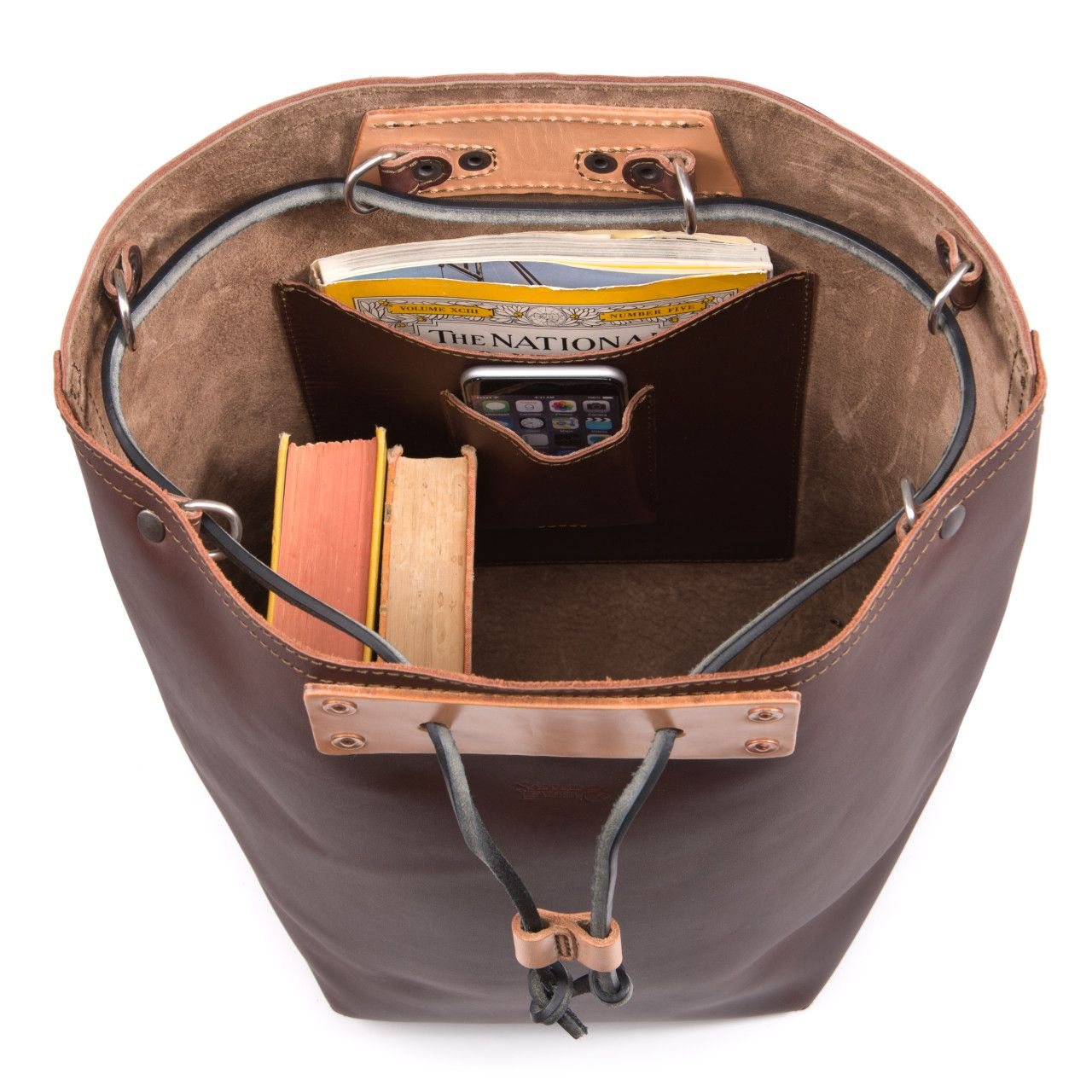 Two books, iphone, map in the inside of the bucket drawstring leather backpack in chestnut leather