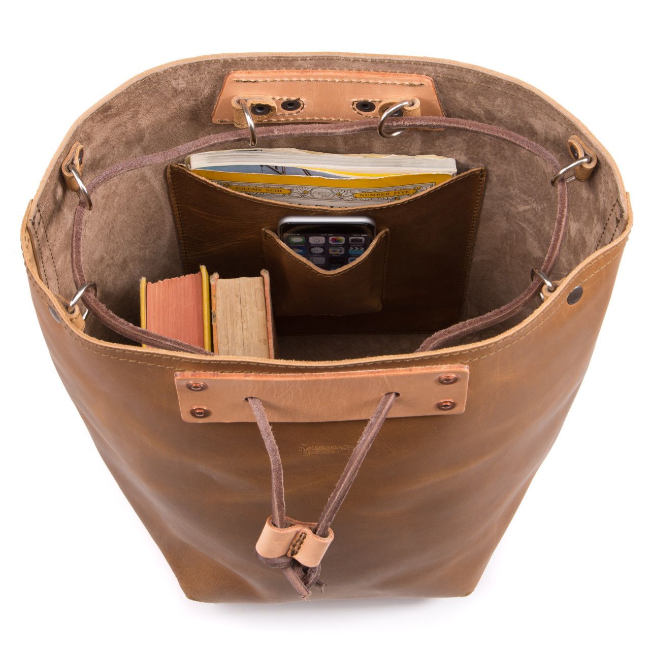 Two books, iphone, map in the inside of the bucket drawstring leather backpack in tobacco leather