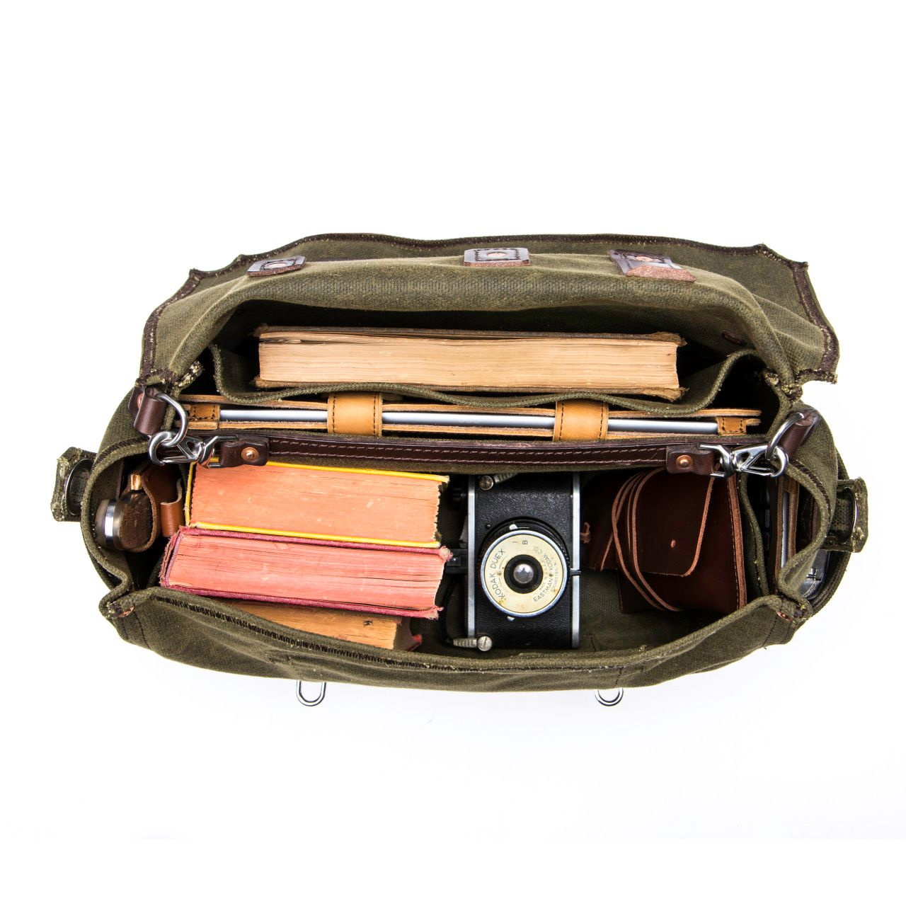 large waxed canvas gear bag in moss green canvas with books, camera and tablet inside