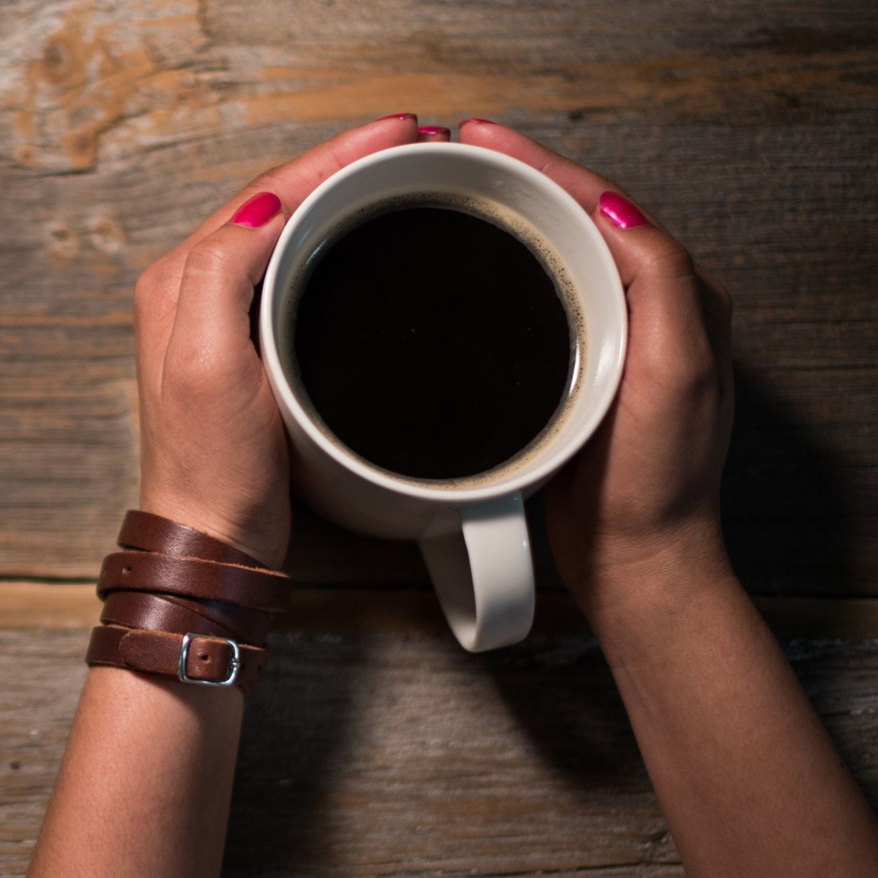 leather wrap bracelet in chestnut leather placed on hands with a cup of coffee