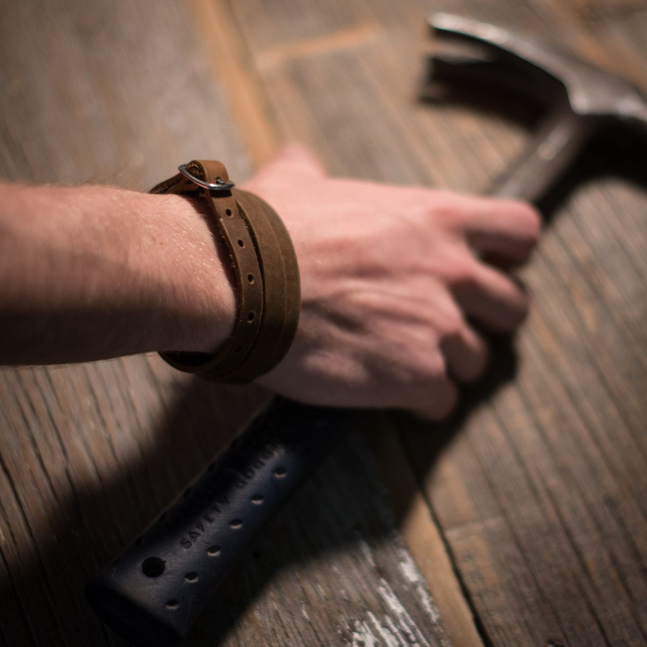 leather wrap bracelet in tobacco leather placed on hands holding a hammer